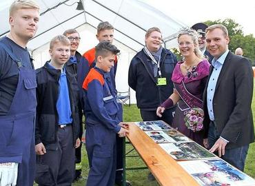 Die Ehrengäste begutachten während des Kreisjugendlagers eine Fotodokumentation der Jugendfeuerwehr aus Spremberg.