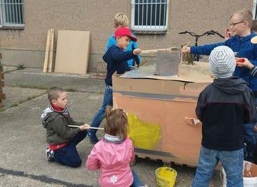 Die Kinder beim Basteln und Bemalen des Hauses
