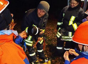 """Christian Beckmann bespricht mit der Feuerwehrjugend in Bagenz, welche Hilfsmittel """"Lotte"""", das Tragkraftspritzenfahrzeug aus Komptendorf, an Bord hat."""
